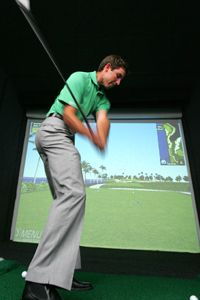 Charl Schwartzel of South Africa swings at a golf simulator in Singapore where the Barclays Singapore Open golf tournament is held.