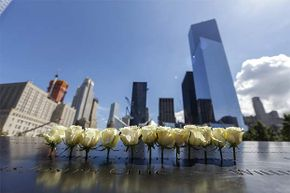 Relatives of the victims of the 9/11 attacks leave flowers, toys and photos on the names written on the monument at the National September 11 Memorial & Museum in New York.