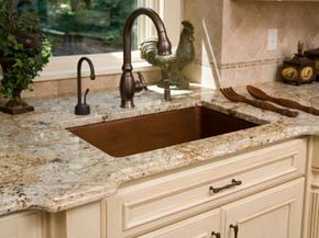 Luxurious kitchen elements including a hammered copper sink basin and granite counter tops. See more pictures of home design.