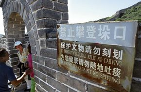 Graffiti stains this archway of the Great Wall of China, despite the nearby sign that forbids desecration of the wall.
