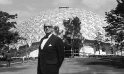 R. Buckminster Fuller, striking a pose in front of a geodesic dome.
