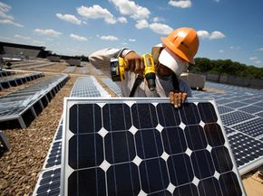 Both white- and blue-collar jobs are turning green. An employee installs photovoltaic solar panels on a roof of a department store. See more global warming pictures.