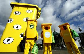 Recyclers are dressed as bins and stand beside the world's largest recycling bin (at around 35 feet in height) in Berlin, Germany during European Recycling Week in 2004.