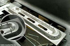 """Burners in gas grills often look like flattened """"O""""s riddled with small holes."""