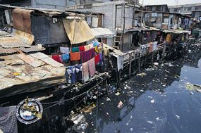 Homes line a polluted canal in Manila, Philippines. This water supply is definitely dirty and most likely infected.