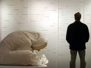 A man views a wall listing the names of 800 out of an estimated 10,000 victims of Nazi experiments as a memorial titled 'Man with Sheet' created by Australian artist Ron Mueck crouches silently at the Medical History Museum in Berlin.