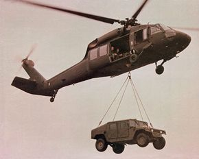 Helicopter airlifting a Humvee