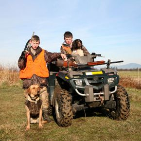Two young hunters with their dogs on ATV.