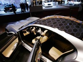 It's too difficult and expensive for solar panels to power the motors in hybrid cars, so they typically assist smaller systems like the air-conditioning unit.