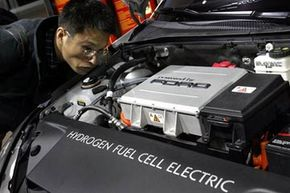 Image Gallery: Hybrid Cars Hyundai Motor Company's Sang-Hee Lee views the hydrogen fuel cell electric power plant in the Ford Focus during media previews at the 2005 North American International Auto Show in Detroit. See more pictures of hybrid cars.