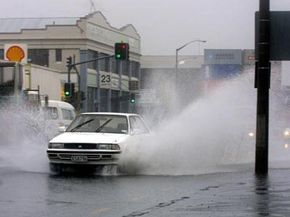 Image Gallery: Car Safety Cars spray water in downtown Auckland, New Zealand, as they drive through deep puddles during heavy rain.