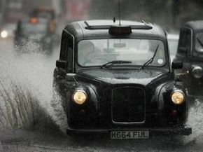 A London taxi cab drives through a patch of standing water, risking hydroplaning, after a heavy downpour.
