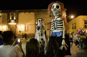 A parade in honor of El Dia de los Muertos passes through a town in Mexico. This is a major holiday in the country.