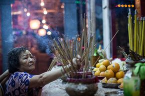 A worshipper makes offerings at a park during the Hungry Ghost Festival on Aug. 14, 2015 in Hong Kong.