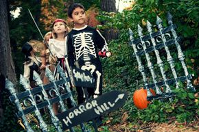 Some pumpkins and hand-painted signs combined with an antiqued fence make for a pretty spooky haunted trail.