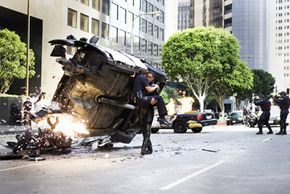 Hancock (Will Smith, right) saves the life of an injured female cop (Liz Wicker, left) - using her battered cruiser as a shield - before taking out a gang of heavily armed bank robbers.