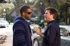 When disgruntled superhero Hancock (Will Smith, left) saves the life of PR exec Ray Embrey (Jason Bateman, right), Ray tries to clean up Hancock's image.