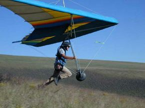 A pilot runs to launch his hang glider.