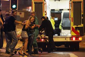 Emergency responders help a clubber into an ambulance to accompany her friend to hospital after the friend collapsed in a club in Bristol, England.