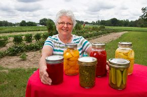 Susiette Jackson poses near her garden with some of the canned goods that she's planning to enter at the state fair. Dill pickles are front right.