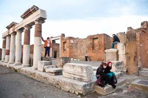 Tourists visit the ruins of the Foro (Forum) at the archeological site in Pompei, Italy. Pompeii was buried in 79, discovered in the 1590s, and rediscovered in the 1700s.