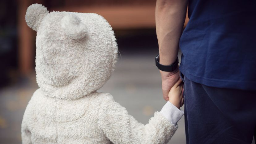 girl in rabbit suit holding father's hand