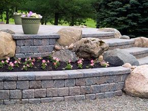 The patio, walls, steps, pots and rocks work together here to form a beautiful hardscape juxtaposed to the flowers, trees and grass of the softscape.