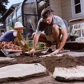 A couple puts down stone flooring.