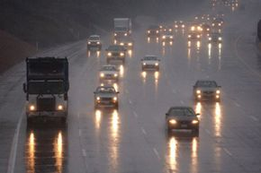 Headlights are reflected on the rain slick freeway during a storm in Inglewood, Calif.