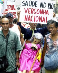 """A protestor holds a sign reading """"Public Health in Rio, National Shame"""" at a 2005 protest in Brazil."""