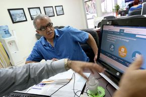 Hisham Uadadeh enrolls in a health insurance plan under the Affordable Care Act with the help of A. Michael Khoury at Leading Insurance Agency in Miami.