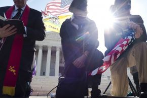 Demonstrators pray outside the U.S. Supreme Court on day three of oral arguments over the constitutionality of the Patient Protection and Affordable Care Act on March 28, 2012.