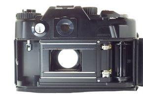 A manual single-lens-reflex camera with an open shutter.