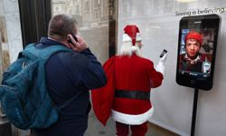 A man looks at a display of a Santa Claus figure with an iPhone at the Apple Store on Regents Street in London, England.