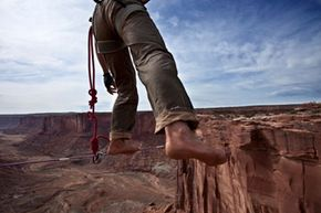 Most highliners wear a safety harness tethered to the rope to prevent them from falling to their deaths if (when) they slip. See more extreme sports pictures.