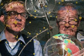Father-and-son research team Luis and Walter Alvarez peer through a star dome, which shows the orbit and location, relative to Earth, of stars and constellations. The Alvarezes postulated that a giant asteroid or comet hit Earth millions of years ago, causing mass extinctions.