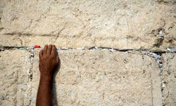 Some worshippers leave written prayers in the wall's cracks.