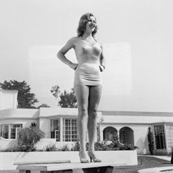 The figure-hugging but low-cut suit of the '30s flattered actress Lana Turner's long legs. (Heels didn't hurt, either.)