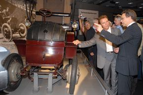Porsche Chief Engineer, Wolfgang Duerheimer, explains to California Governor Arnold Schwarzenegger that the Lohner-Porsche was the first advanced electric car and the technological star of the 1900 Paris Auto Show.