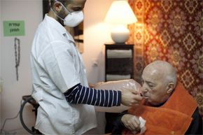 A nurse helps a patient to inhale cannabis fumes from a vaporizer at an Israeli nursing home on March 9, 2011. Together with Israel's health ministry, the Tikon Olam company currently is distributing cannabis for medicinal purposes to more than 1,800 people in Israel.