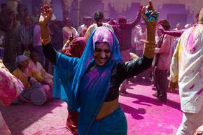 A woman in Uttar Pradesh dances in the cloud of Holi colors.