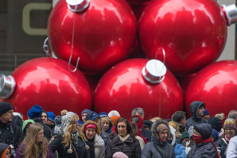 People wait for Macy's annual Thanksgiving Day parade in 2014 under a display of giant ornaments at the store. People grumble that Christmas starts earlier each year — a dispute at least 100 years old. Zoran Milich /Getty Images