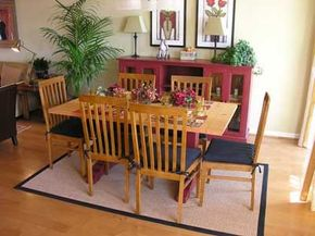 Light-colored furniture and plants create a homey feeling                              around this cozy dining room table.