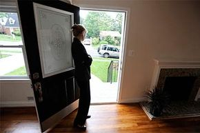 A real estate agent stands at the door of a house in Silver Spring, Maryland, where she held an open house in 2010 at the height of the homebuyer tax credit buying rush.
