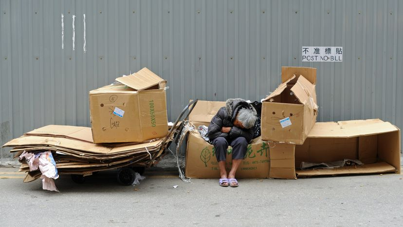 Homeless person asleep on cardboard boxes