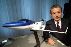 Takeo Fukui, President and Representative Director of Honda Motor Co., Ltd. stands next to a model of HondaJet at a media conference on Dec. 17, 2003 in Tokyo, Japan.