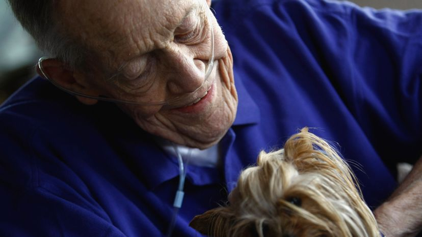 Bud Anderson holds a therapy dog named Sally Sue, during a hospice visit at his house on Aug. 31, 2009.  John Moore/Getty Images