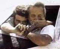 A hijacker threatens Captain John Testrake as he leans from the cockpit of TWA Flight 847 in Beirut, June 1985.
