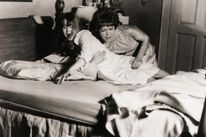 "In this scene from ""The Exorcist,"" mom Chris MacNeil (Ellen Burstyn) struggles to keep her demonic daughter (Linda Blair) in bed."
