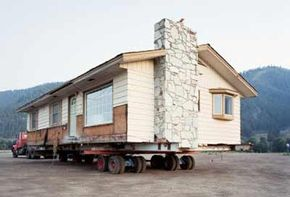 House movers have the jacks, steel beams and dollies you'll need to get to this point.